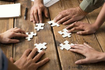 Viele Hände halten jeweils ein Puzzleteil.