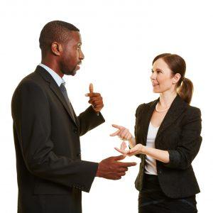 Mann und Frau reden als Geschäftsleute gestikulierend miteinander